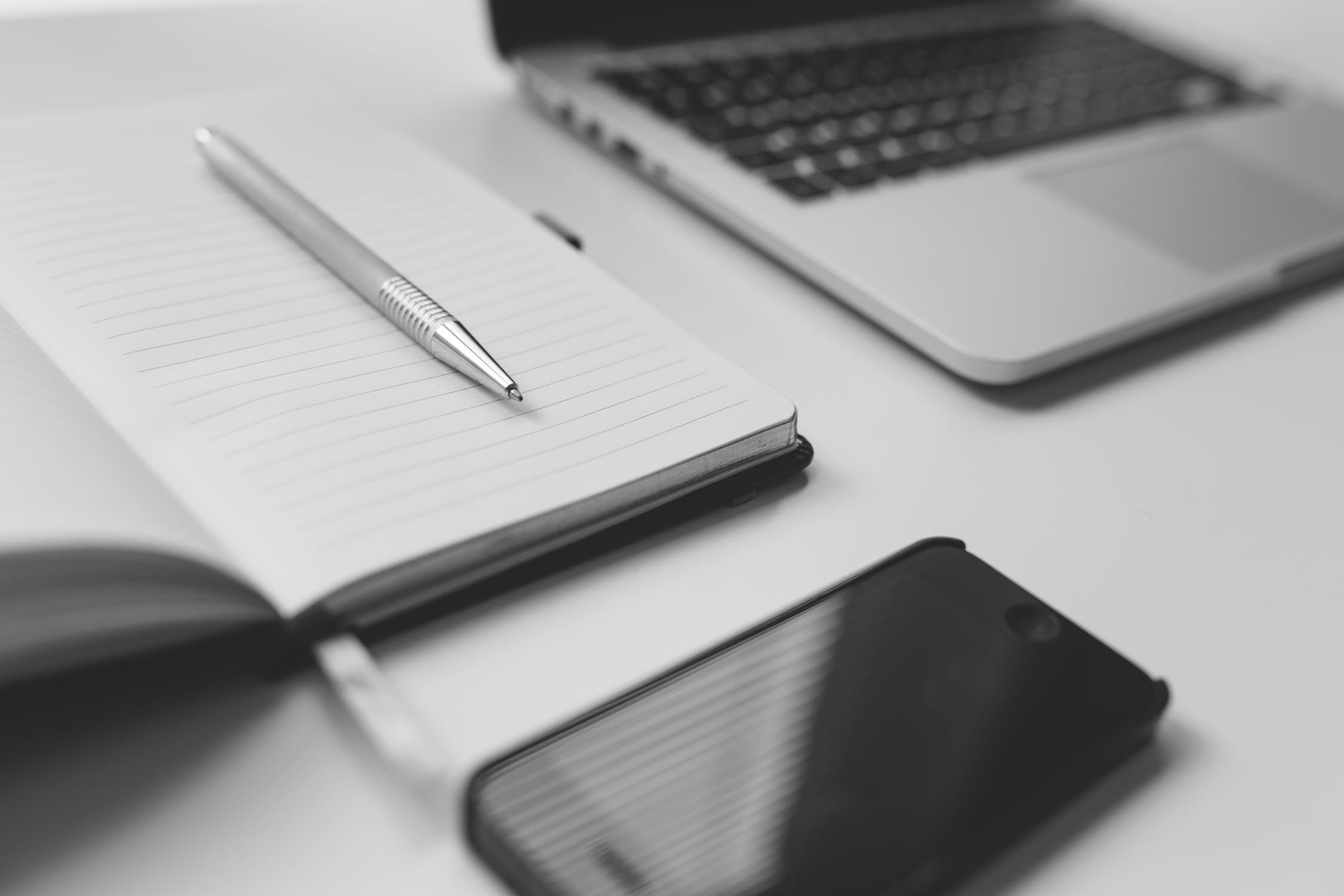 Services - Ein Büroschreibtisch mit Laptop, Block und Smartphone.