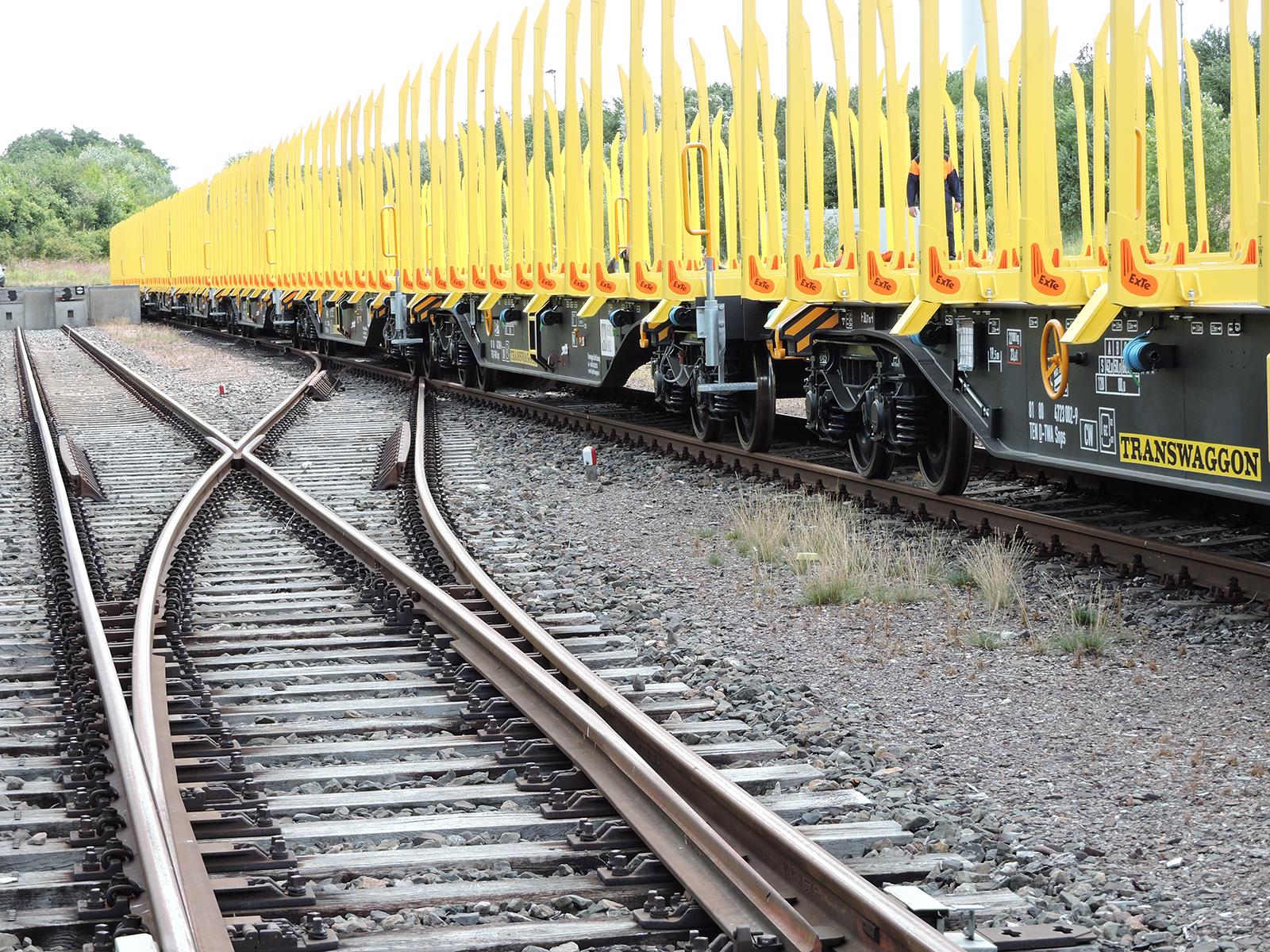 Ein Holzwaggon der Gattung SNPS der Transwaggon GmbH in gelb.